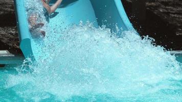 niño bajando tobogán de agua en cámara super lenta video