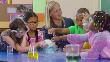 Teacher and group of students make a science experiment in school classroom video