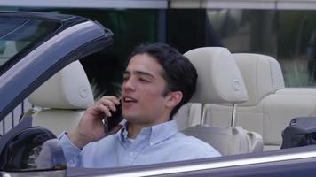 giovane uomo d'affari che entra in un'auto convertibile mentre parla al cellulare video