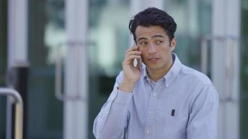 giovane uomo d'affari che parla al cellulare all'aperto video