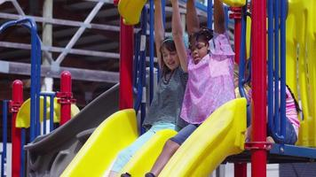 Girls going down slide on school playground video