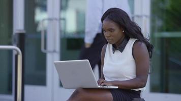 Businesswoman using laptop outdoors video