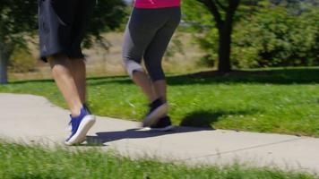 Couple running at park, closeup of feet video