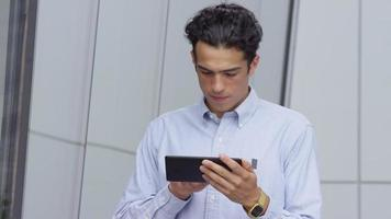 Young businessman using digital tablet outdoors video