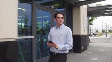 giovane uomo d'affari che cammina e usa il cellulare video
