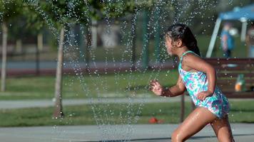 niña jugando en el aspersor en el parque en cámara super lenta video