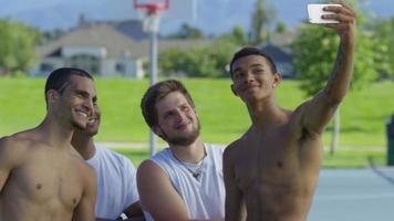 gruppo di giocatori di basket adolescenti che guardano il cellulare video