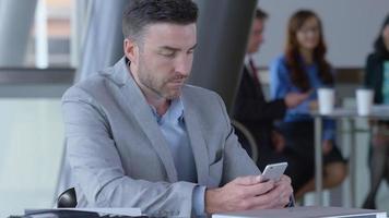giovane uomo d'affari che usa il cellulare nella hall dell'ufficio? video
