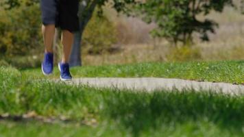 Man running on trail at park, closeup of feet video