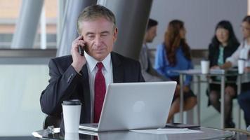 uomo d'affari maturo tramite telefono cellulare nella hall dell'ufficio video