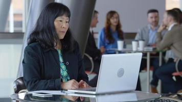 Mature Asian businesswoman using laptop computer in office lobby video
