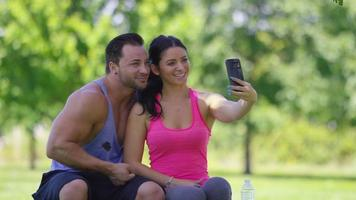 Athletic couple at park take selfies together video