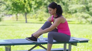 Athletic woman at park stretches before run video