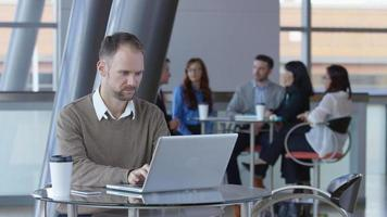 Young businessman using laptop computer in office lobby video