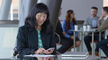 matura imprenditrice asiatica utilizzando il cellulare nella hall dell'ufficio video