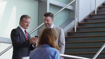 due uomini d'affari che si incontrano sulle scale della hall dell'ufficio guardando il cellulare video