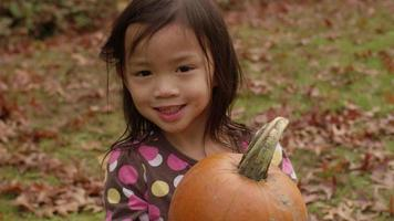 Young girl in Fall holding pumpkin video