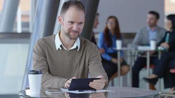 Young businessman using digital tablet in office lobby video
