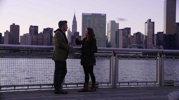 Couple in New York City stand by river talking with skyline in background video