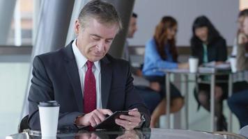 Mature businessman using digital tablet in office lobby video