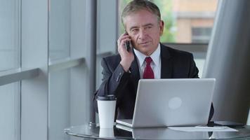 empresário maduro falando no celular no saguão do escritório video