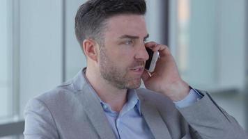 jovem empresário usando telefone celular no saguão do escritório video