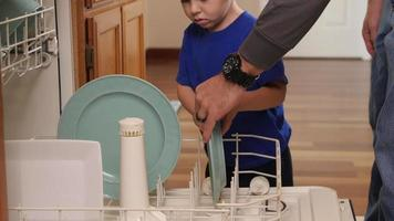 Father and Son loading dish washer together video