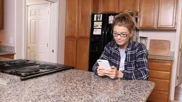 Young woman using smart phone in kitchen at home video