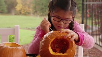 junges Mädchen, das Kürbis für Halloween schnitzt video