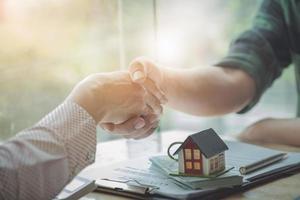 Los agentes inmobiliarios acuerdan comprar una casa y entregar las llaves a los clientes. foto