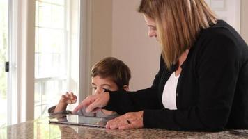 mor och son använder digital tablet tillsammans video