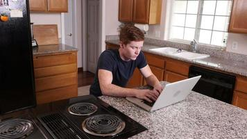 Young man working on laptop computer in kitchen at home video