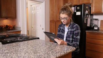 giovane donna che utilizza tavoletta digitale in cucina a casa video