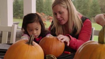 Mama und Kinder schnitzen Kürbisse für Halloween video