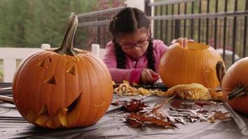 junges Mädchen, das Kürbisse für Halloween schnitzt video
