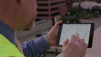 superviseur de la construction à la recherche de plans sur tablette numérique video