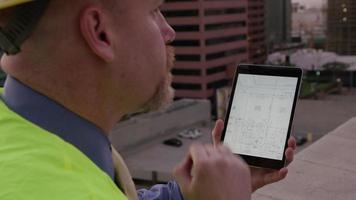 directeur de construction regardant des plans sur l'écran tactile video
