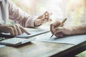 Agentes inmobiliarios discutiendo préstamos y tasas de interés para comprar casas. foto
