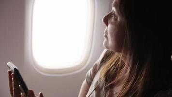 primo piano di una donna che usa il cellulare in aereo video