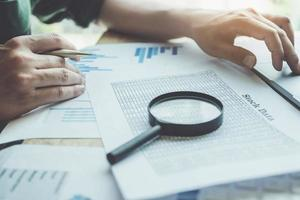 Businessman using magnifying glass to review balance sheet photo