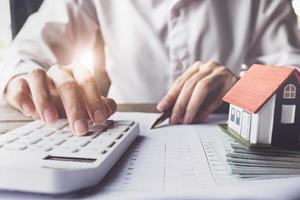 el cliente usa bolígrafo y calculadora para calcular el préstamo para la compra de una vivienda foto