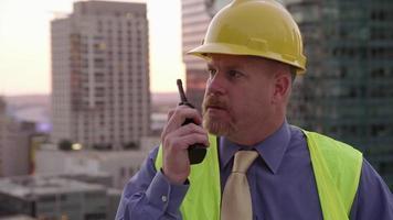directeur de construction sur le toit parlant sur talkie-walkie video