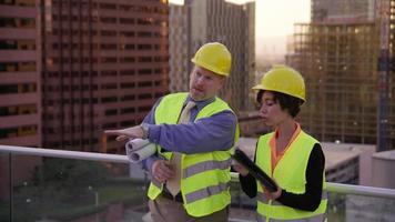 deux superviseurs de construction examinent les plans sur le toit video