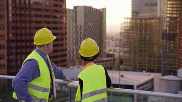 deux superviseurs de la construction regardent les toits de la ville depuis le toit video