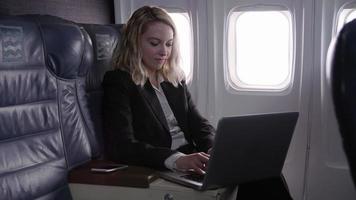 donna d'affari che utilizza il computer portatile in aereo video