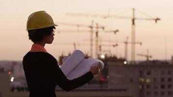 architecte tenant des plans regardant le chantier de construction au coucher du soleil video