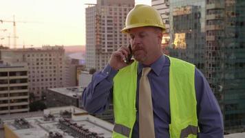 directeur de la construction sur le toit à l'aide d'un téléphone portable video