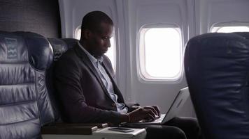 uomo d'affari che utilizza computer portatile in aereo video