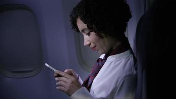 assistente di volo che usa il cellulare di notte video
