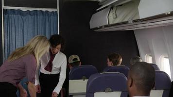 assistente di volo che aiuta il passeggero con i bagagli video